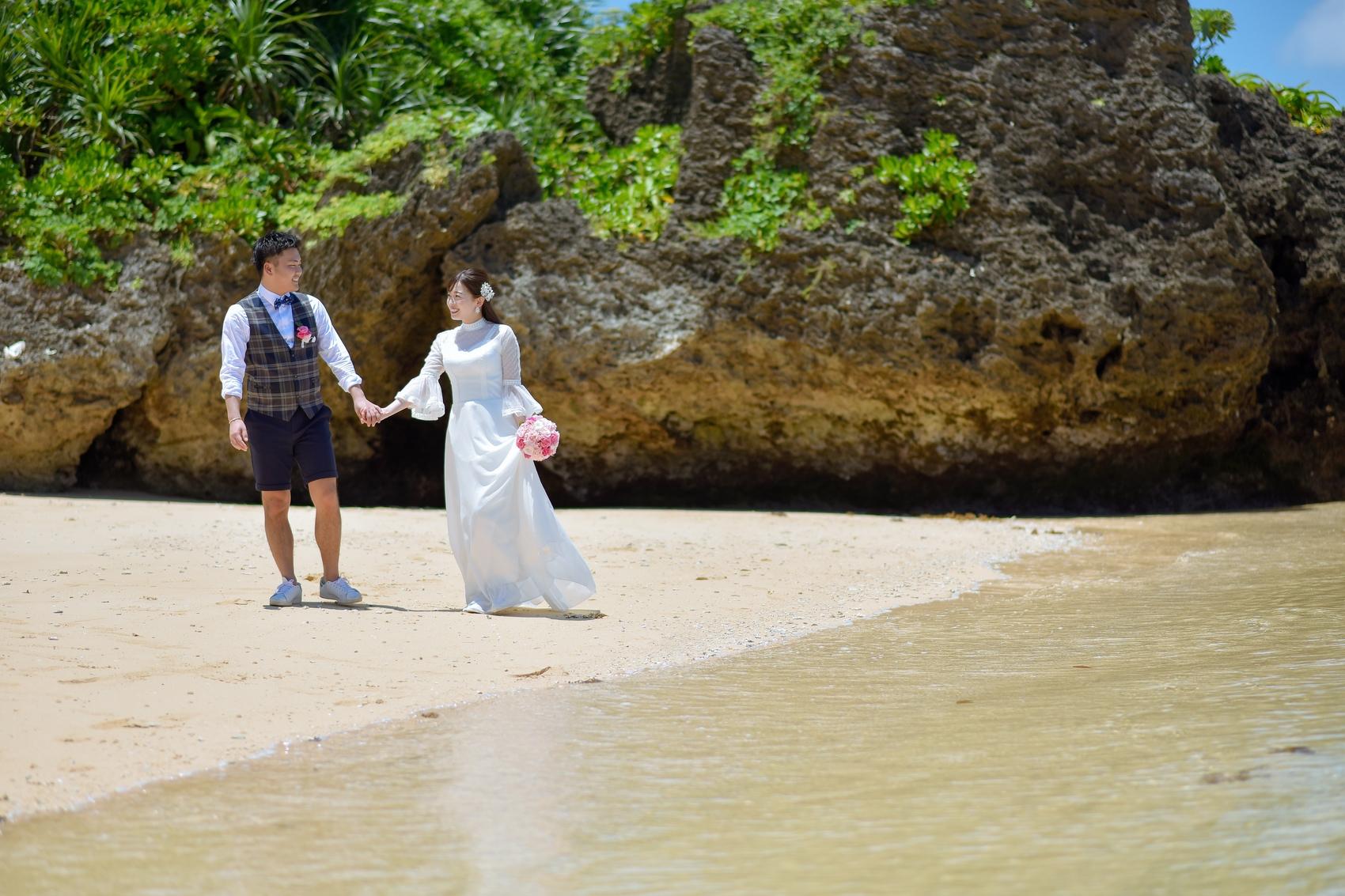 手を繋いで砂浜を歩く新郎新婦