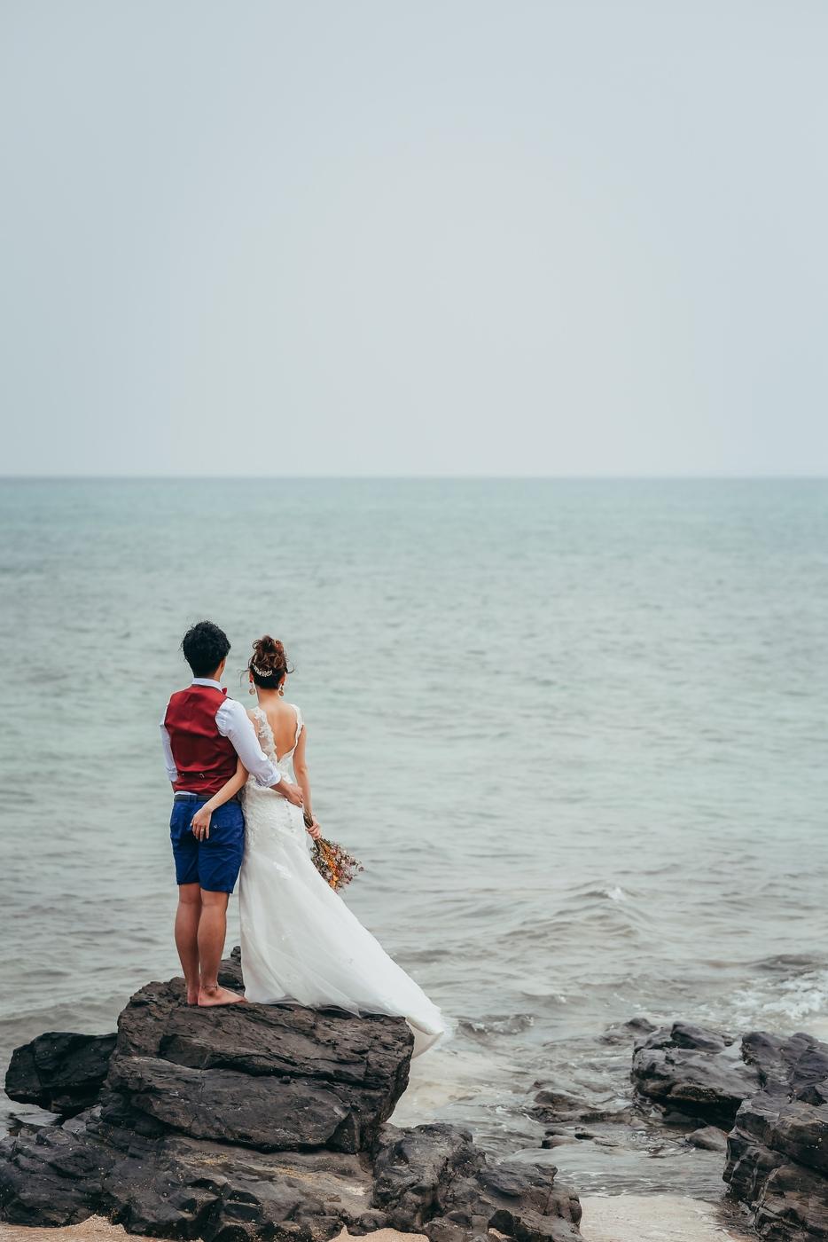 岩場に立って海を眺める